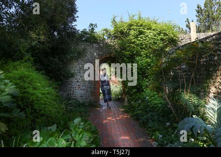 Una giovane donna in piedi all'interno di un arco in mattoni in giardini di Kipling, Rottingdean, Brighton, Regno Unito Foto Stock