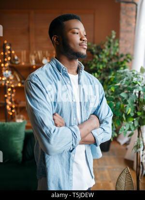Uomo nero con un astuto guardare nel soggiorno relax a casa. Giovane americano africano persona di sesso maschile in piedi nella sua casa Foto Stock