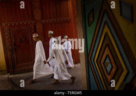 Omani giovani uomini che indossano tradizionali abiti arabi nel Souk di Nizwa, Oman Foto Stock