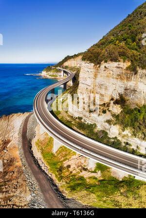 New Scenic 5 posti Grand Pacific Highway drive passando scogliera sul mare attorno al ponte di pietra arenaria ripida scogliera sulla costa del Pacifico in Australia - antenna vista verticale oltre il Foto Stock