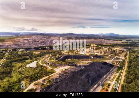 Aprire enorme nero tagliato miniera di carbone nella Hunter Valley regione rurale di Australia lo scavo di combustibile fossile per electrisity stazione di potenza elevati vista aerea Foto Stock