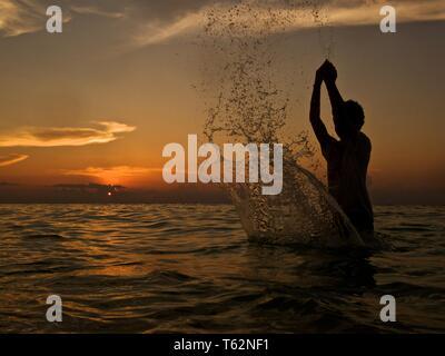Un giovane ragazzo, visibile solo in silhouette, giocando sulla spiaggia al tramonto Foto Stock