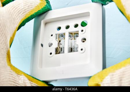 Mettere una parte superiore sul nuovo doppio interruttore posizionato nel connettore a presa all'interno del muro a secco dal lavoratore, lavori elettrici. Foto Stock