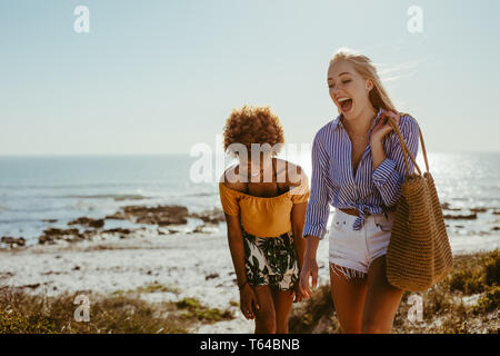 Due felici donne camminando lungo la spiaggia. Amici di sesso femminile sorridere mentre camminando insieme in riva al mare.