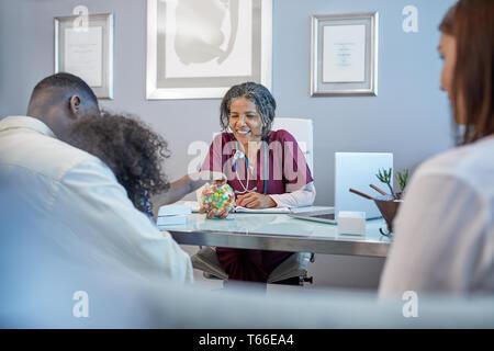 Medico donna dando caramella alla ragazza in ufficio medici