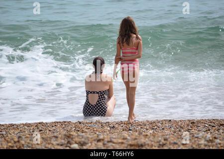 Due giovani ragazze in costumi da bagno, sul mare e sulla spiaggia che si affaccia sul mare azzurro e bianco onde shore Foto Stock