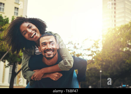 L uomo dando piggyback ride per donna Foto Stock