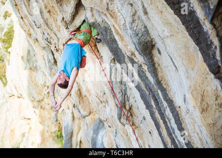 Maschio di rocciatore appeso a testa in giù sul percorso impegnativo, prima di appoggio mantenendo sul suo tentativo Foto Stock