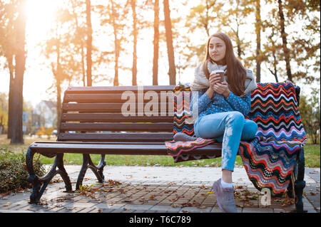 Giovane e attraente ragazza seduta su una panchina nel parco di autunno e di bere il caffè Foto Stock