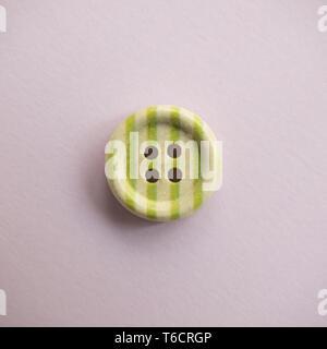 Isolate il pulsante di legno colorato con strisce colorate su una luce sfondo rosa, cucitura