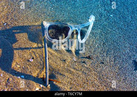 Un vecchio paio di abbandono di bianco e trasparente in plastica sinistra occhiali da sole sulla spiaggia sabbiosa. oggetti spezzati e inquinamento atmosferico. plastica inquina th Foto Stock