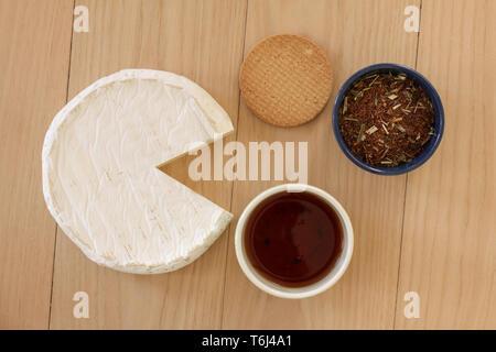 Round formaggio brie con tazza di tè, biscotti e foglie di tè in una ciotola su sfondo di legno. Vista superiore moderno e minimalista dell'immagine. Foto Stock