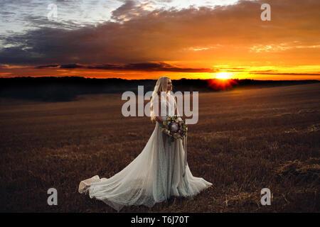 Bella Sposa in posa di campo al tramonto. Foto Stock