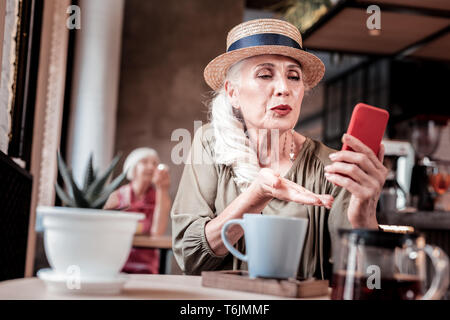 Ben mantenuta senior lady nel cappello di paglia di parlare attraverso messaggi video Foto Stock