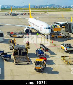 I passeggeri in partenza in aereo, servizio di autobus, passerella, trasportatori di bagagli in pista nel sole splendente, aeroporto di Istanbul, Turchia Foto Stock