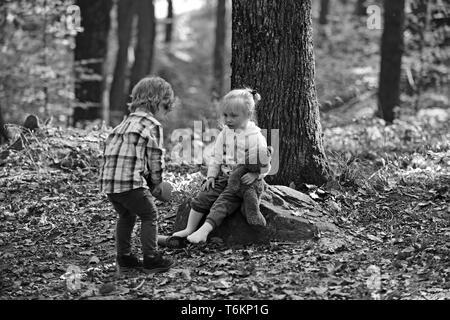 Fratello aiutare la sorella a mettere stivali rossi. Little Boy mettere scarpe sulla ragazza piedi. Mano concetto. I bambini preparano per camminare nella foresta di autunno Foto Stock