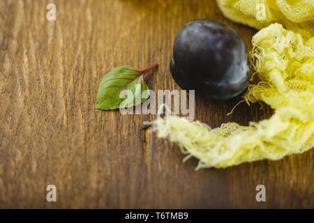 Le prugne su sfondo di legno Foto Stock