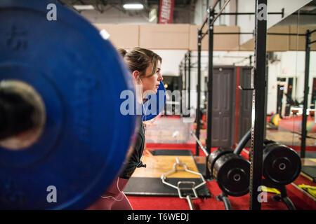 Vista laterale della bella donna facendo un barbell squat in studio fitness