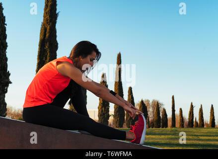 Giovani runner donna gambe stretching prima di correre in un parco. Close up atletico e sana bambina indossa bianco e rosa sneakers.