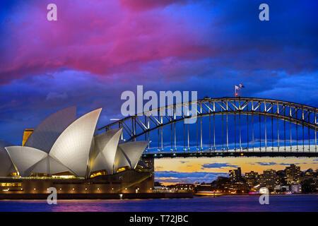Famosa in tutto il mondo la Sydney Opera House e Harbour Bridge al tramonto. Nuvole sfocata e luci dei punti di riferimento riflettono in acque sfocata del porto. Sydney, Nuovo
