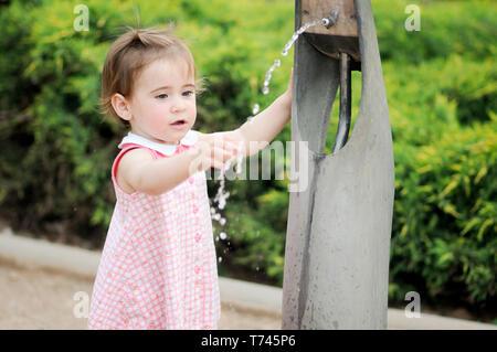 Bambina di acqua potabile in un parco fontana Foto Stock
