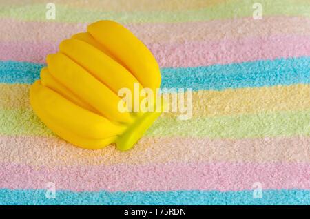 Aroma organico sapone in forma di banana su un asciugamano multicolore. Cura di bellezza concetto. Spazio di copia Foto Stock