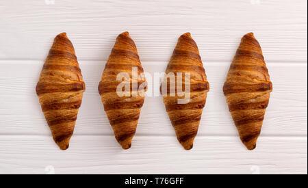 Croissant appena sfornati in bianco sullo sfondo di legno. Vista superiore Foto Stock