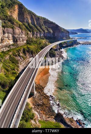 Moderna autostrada della scogliera sul mare attorno al ponte di ripide scogliere di arenaria su Australian Pacific Coast - parte del Grand Pacific drive. Antenna verticale panora Foto Stock