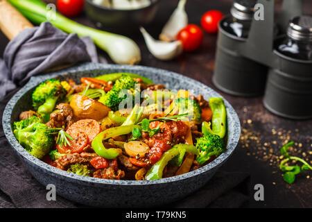 Frittura di carne di manzo stroganoff con patate, broccoli, mais, pepe, carote e salsa in una padella, sfondo scuro.