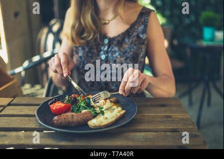 Una giovane donna è avere la prima colazione con la salsiccia in un ristorante all'aperto