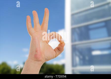 Primo piano dell'uomo che mostra bene gesto con le dita nella parte anteriore dell'edificio in vetro Foto Stock