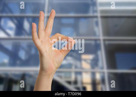 Donna con palazzo di vetro come sfondo che mostra bene gesto con le dita in primo piano Foto Stock