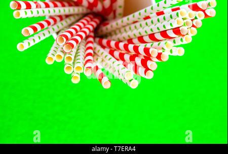 Paillette rosso per il succo in un bicchiere di carta su uno sfondo verde. Foto Stock