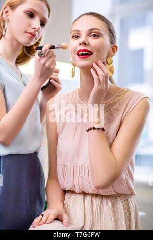 Piacevole bella donna pensare circa il suo look Foto Stock