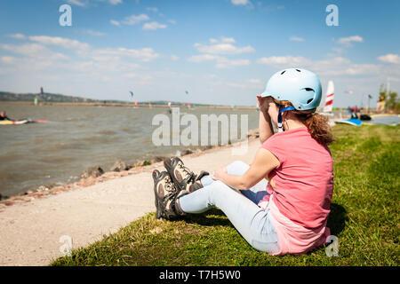 Chiudere l immagine di una donna indossare in linea di lame a rullo in prossimità di un filamento di un lago