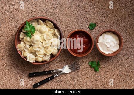 Cibo russo pelmeni carne gnocchi con panna acida e ketchup disposti in una fila sulla pietra marrone sfondo . Vista aerea, copia dello spazio. Foto Stock
