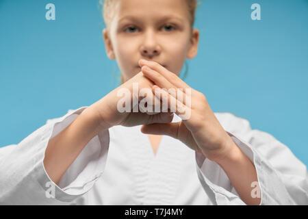 Messa a fuoco selettiva di piccole mani di una ragazza che mostra il pugno in studio. Carino donna bambino guardando la fotocamera e in posa sul blu sfondo isolato. Giovani fighter training e praticare il karate. Concetto di sport. Foto Stock
