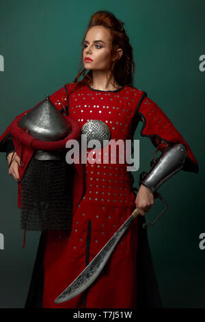 Donna Gorgeous warrior holding pugnale medievale e casco, indossa in rosso tunica medievale. Bella donna con labbra rosse e zenzero capelli in posa di studio, guardando lontano. Foto Stock