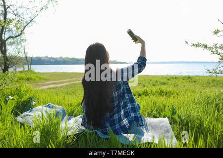 Bella giovane donna prendendo selfie vicino al fiume Foto Stock