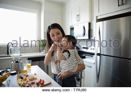 Alimentazione madre figlia dei bimbi in cucina Foto Stock