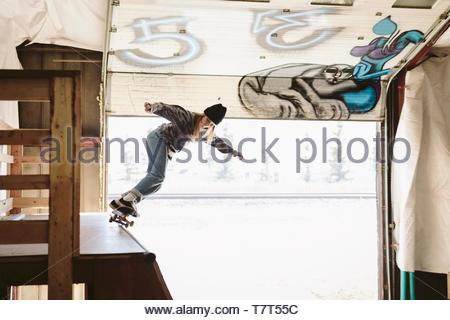 Ragazza adolescente lo skateboard nella parte superiore della rampa a indoor skate park Foto Stock
