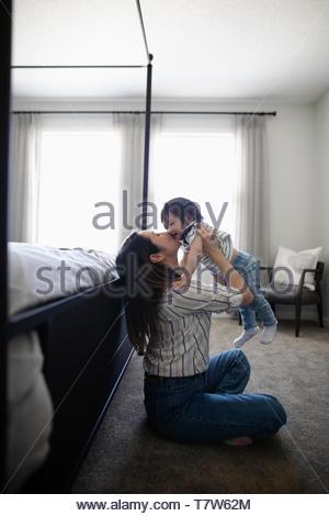 Affettuosa madre baciare toddler figlia in camera da letto Foto Stock