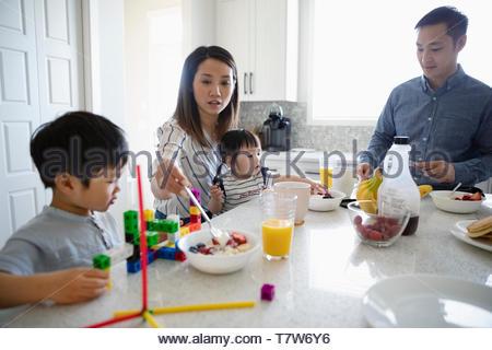 Famiglia di mangiare la colazione e giocare con i giocattoli in cucina Foto Stock
