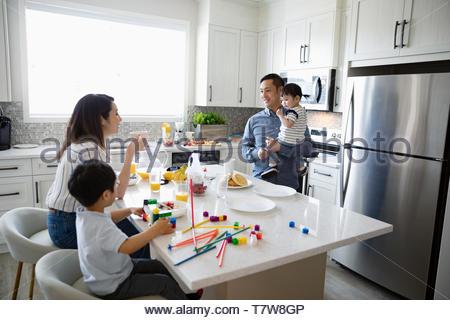 Famiglia di mangiare la colazione e giocare con i giocattoli in cucina di mattina Foto Stock
