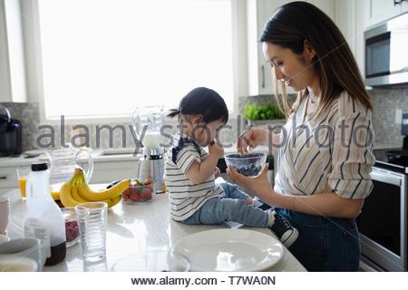 Madre e figlia toddler mangiare mirtilli in cucina Foto Stock