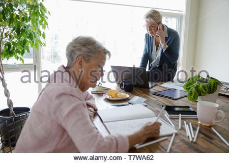 Donna che lavorano al computer portatile mentre senior colori madre nel libro da colorare Foto Stock