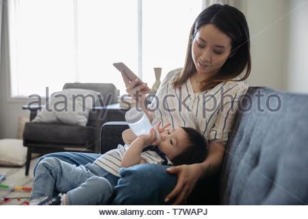 Madre guarda la figlia dei bimbi con biberon Foto Stock