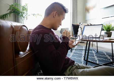 Uomo che lavora da casa, utilizzando smart phone Foto Stock
