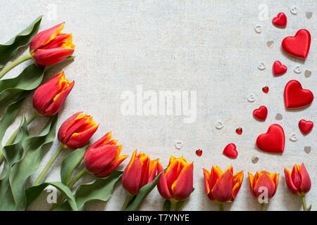 Frontiera con il rosso e tulipani gialli e cuori su sfondo chiaro - testo spazio, biglietto di auguri Foto Stock