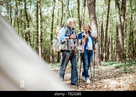 Bella coppia senior escursionismo con zaini e bastoncini da trekking nella foresta. Concetto di stile di vita attivo su pensionamento